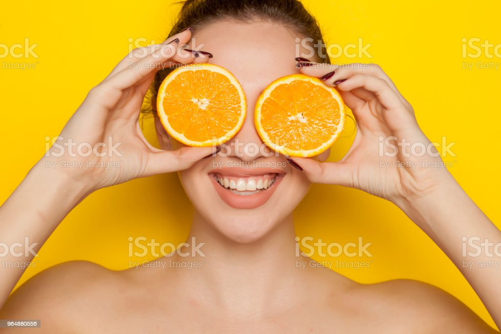 Happy young woman posing with slices of oranges on her face on yellow background royalty-free stock photo