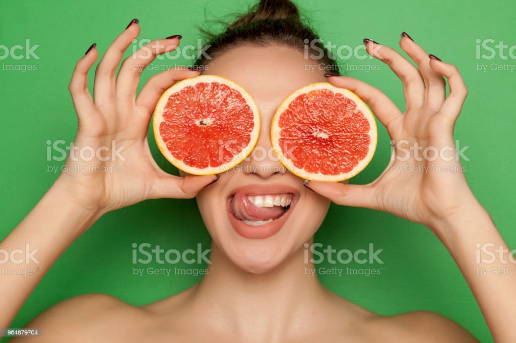 Happy young woman posing with slices of red grapefruit on her face on green background royalty-free stock photo