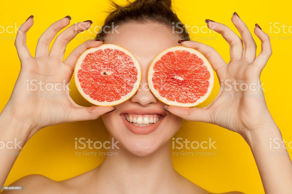 Happy young woman posing with slices of red grapefruit on her face on yelow background royalty-free stock photo