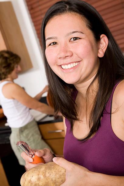 glückliche junge frau vorbereitung abendessen in ihrer küche - peeling zu hause machen stock-fotos und bilder
