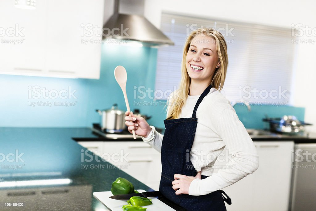 Happy young woman preparing food in elegant kitchen stock photo