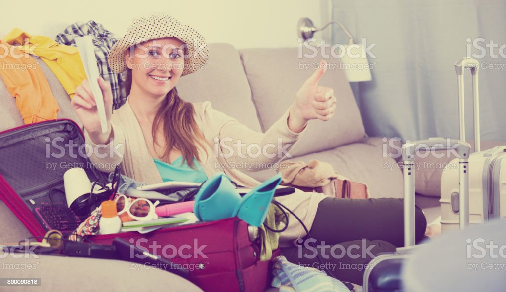 Happy young woman preparing to depart for holiday stock photo