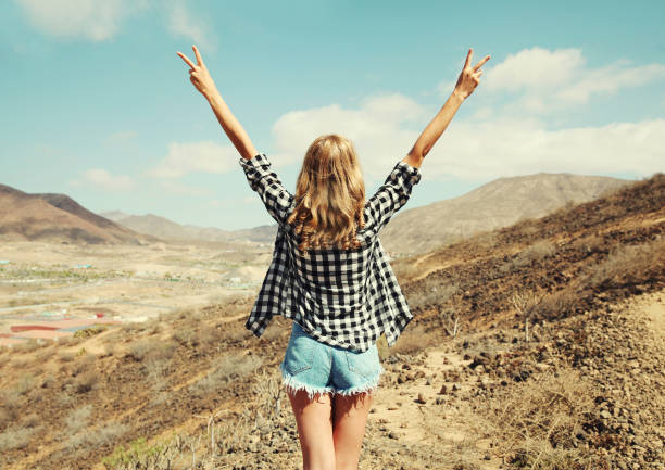 Happy young woman raises hands up on a hiking trail on top of the mountain, view from the back, Tenerife, Canary Islands, Spain stock photo