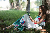 Happy young woman reading a book in public park
