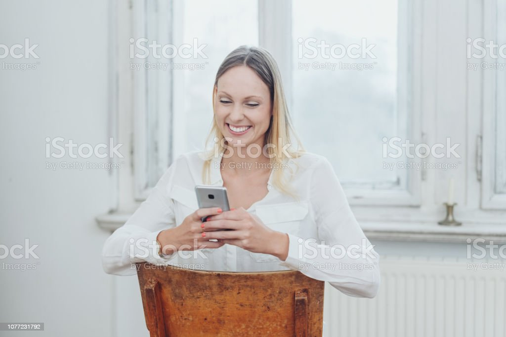 Happy young woman reading a text message