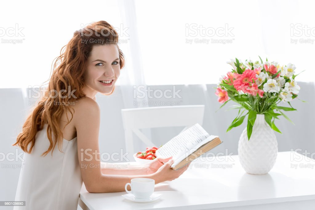 happy young woman reading book while sitting at table with coffee cup and flowers in vase stock photo