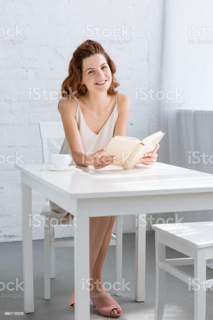 happy young woman reading book with coffee cup on table at home stock photo