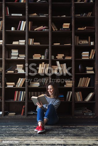 Happy young woman with a book in front of the bookshelves