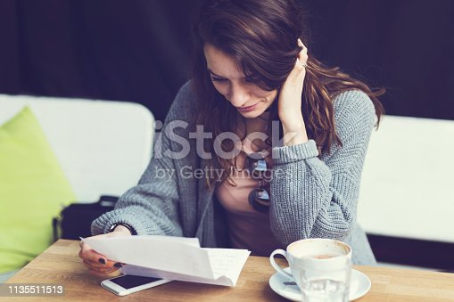 Beautiful young woman reading letter and feeling happy