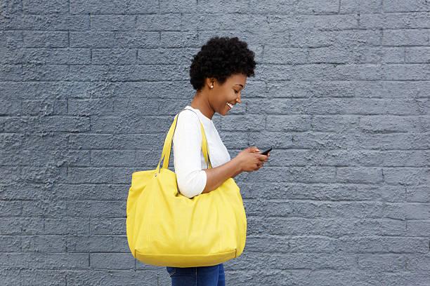 glückliche junge frau liest nachricht an mobiltelefon - handytasche stock-fotos und bilder