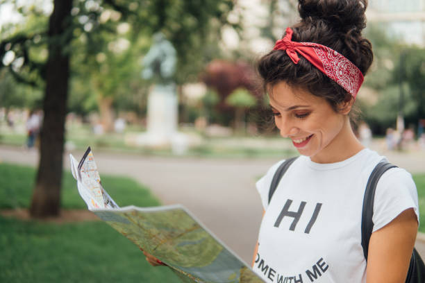 Happy young woman reading thye map and smiling stock photo