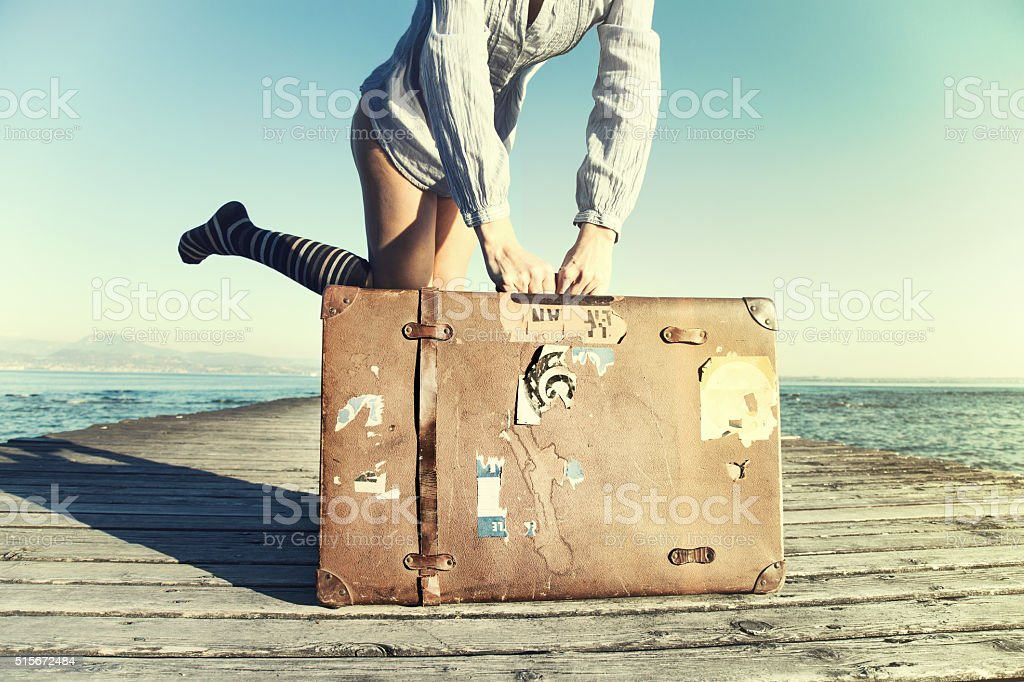 happy young woman ready to travel with her suitcase stock photo