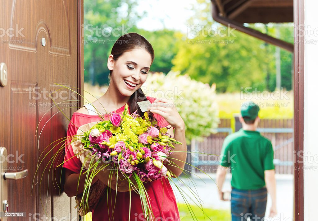 Happy young woman receiving flowers Happy young woman standing in an entance door, holding a bouquet of flowers and reading label. Delivery man in the background.  20-24 Years Stock Photo