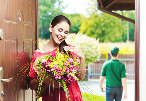 Happy Young Woman Receiving Flowers Stock Photo - Download Image Now