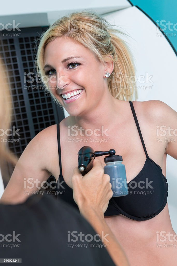 Happy young woman receiving spray tan treatment at the spa stock photo