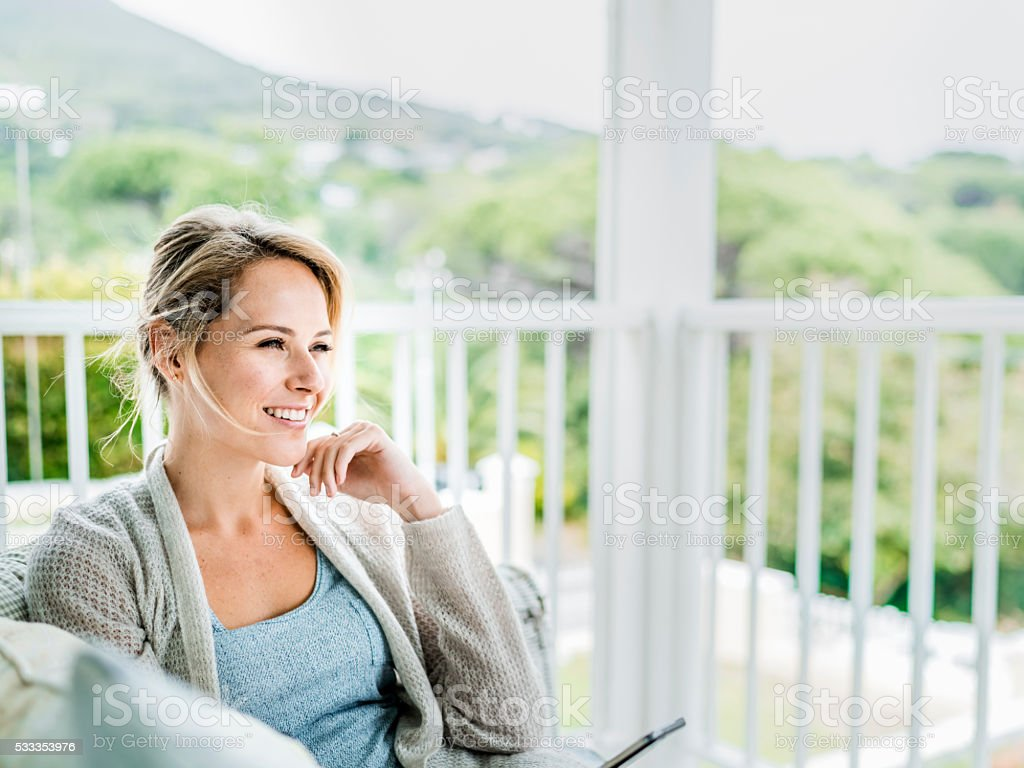 Happy young woman relaxing on balcony stock photo