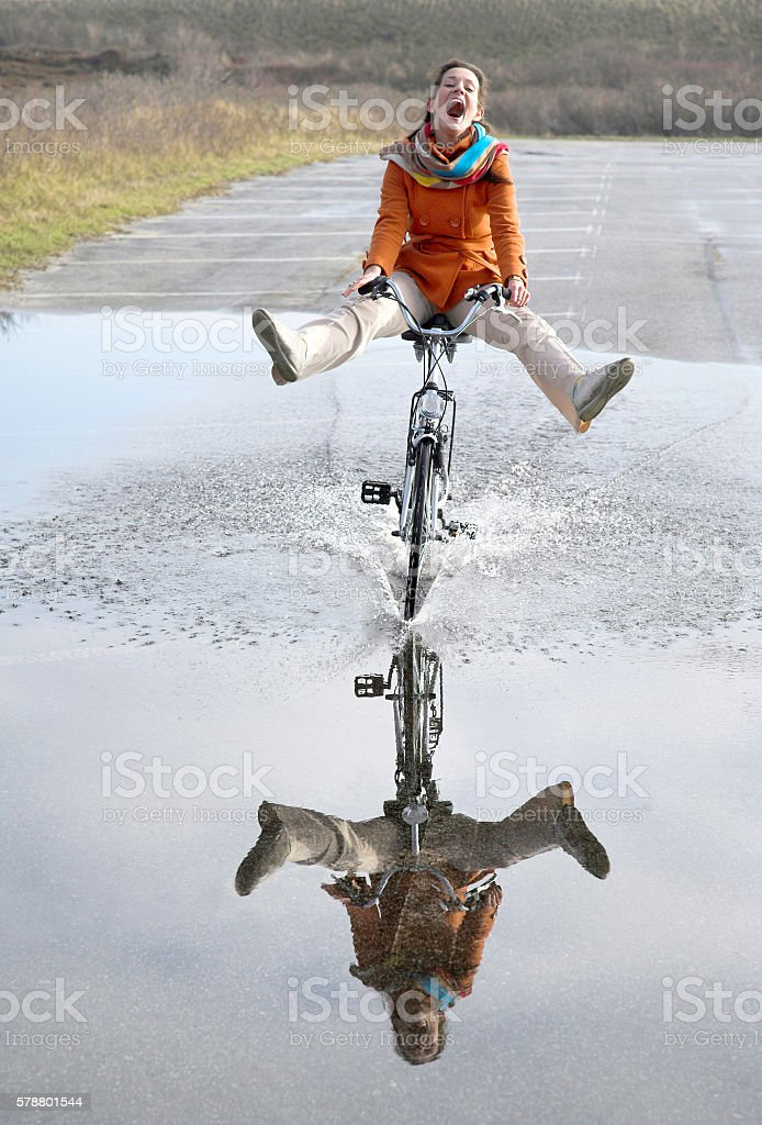 Happy Young Woman Riding Bicyle Through Large Puddle with Reflection stock photo