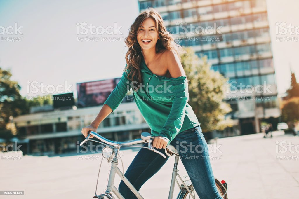 Happy young woman riding bike on a sunny day stock photo