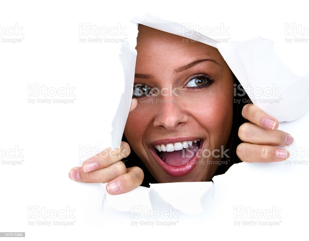 Happy young woman ripping through paper wall royalty-free stock photo