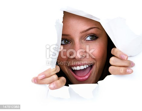 Happy young woman ripping through white paper