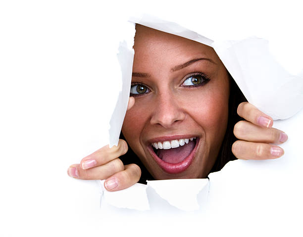 Happy young woman ripping through paper wall stock photo