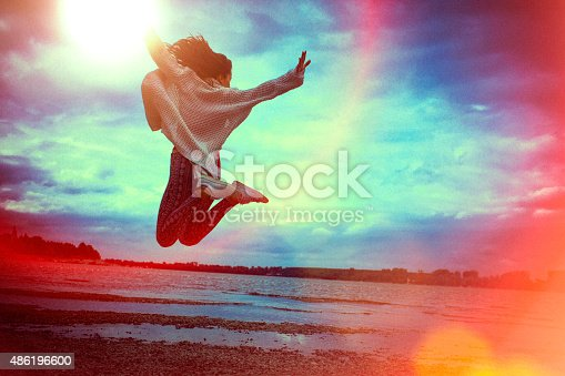 A happy young woman jumping and flying in the air across the beach. The woman's arms and legs are wide spread. She wears red t-shirt, yoga pants and a white vest. The blue cloudy sky is in the beckground;