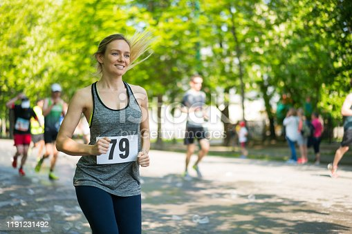 smiling woman outdoors in spring running marathon sports event, background blurred, copy space