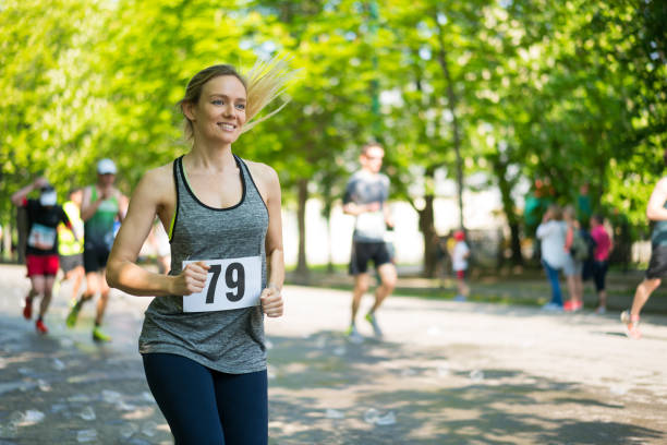 happy young woman running marathon on sunny day in spring stock photo