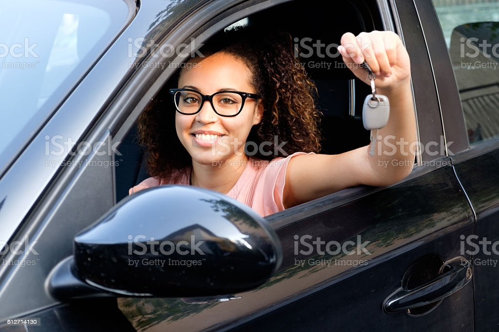 Happy young woman seated in her new car – Foto