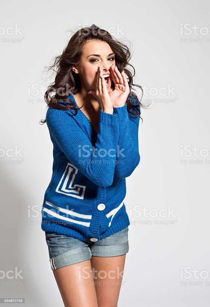 Happy young woman shouting Portrait of happy young woman wearing blue cardigan and shorts shouting. Studio shot, white background. 20-24 Years Stock Photo