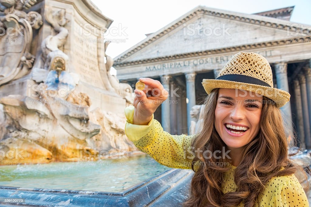 Happy young woman showing coin near fountain in rome, italy stock photo