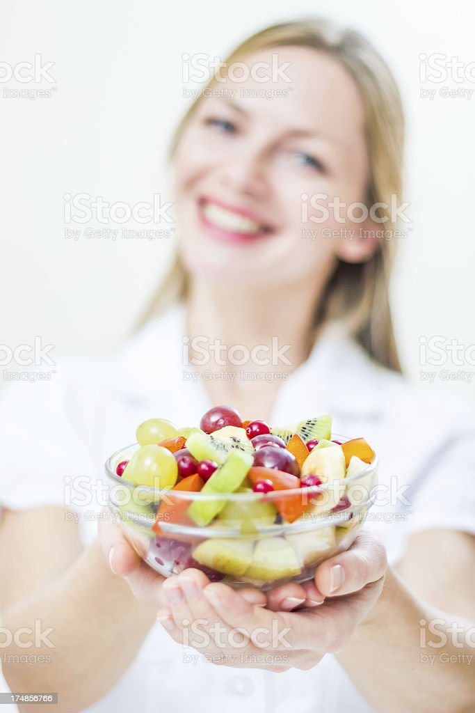 Happy young woman showing fruit salad, smiling, posing. Healthy lifestyle. royalty-free stock photo