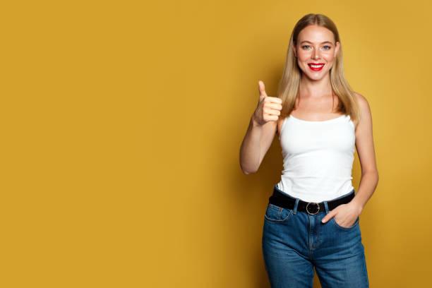 glückliche junge frau zeigt daumen nach oben auf gelbem hintergrund. positive emotionen - natürliche make up kurse stock-fotos und bilder
