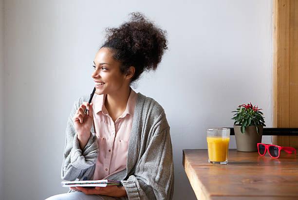 Mulher jovem feliz sentada em casa com papel e caneta - foto de acervo
