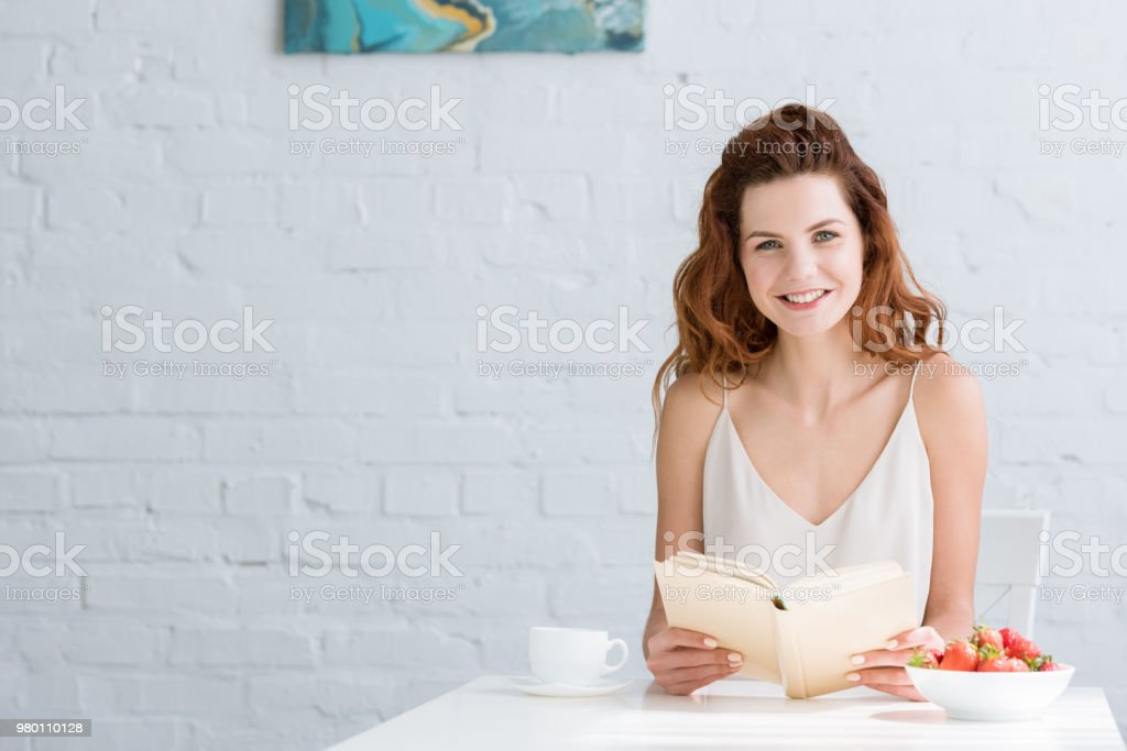 happy young woman sitting at table with coffee and strawberry and reading book at home stock photo