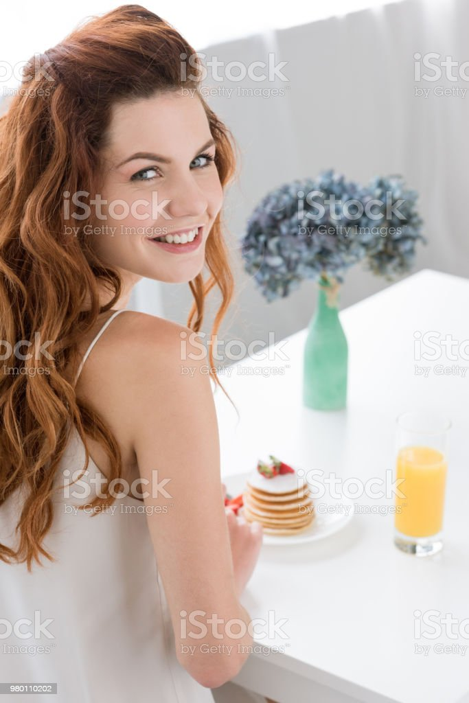 happy young woman sitting at table with pancakes and orange juice at home stock photo