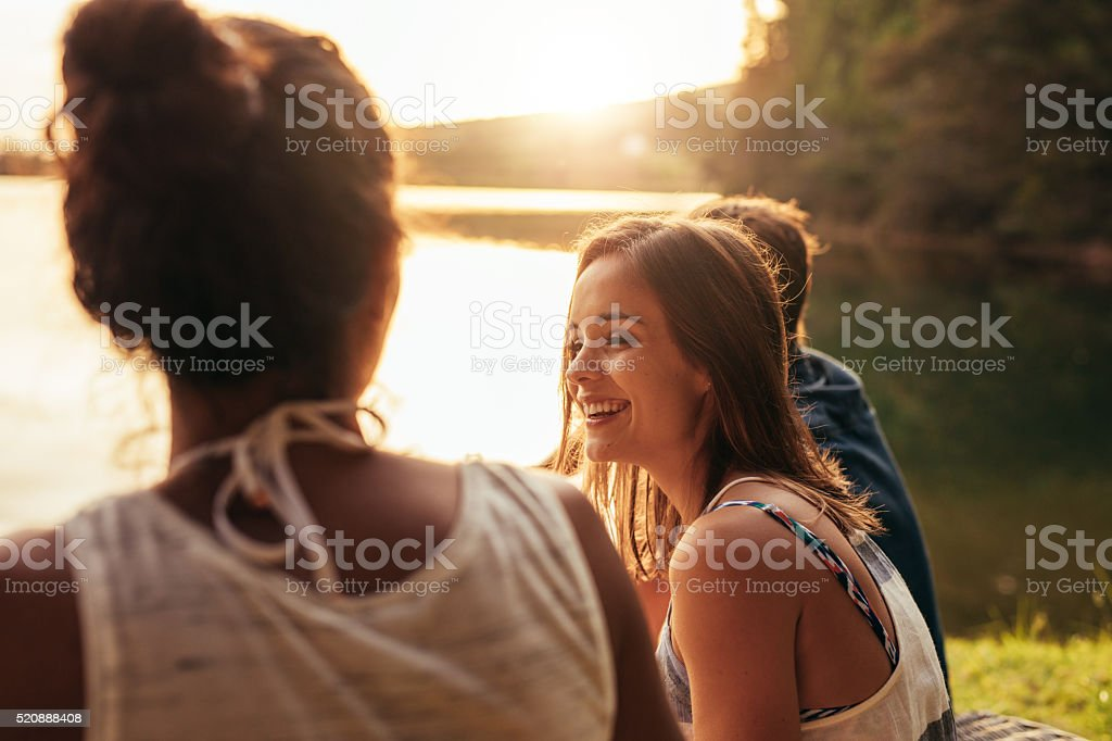 Happy young woman sitting by a lake with her friends stock photo