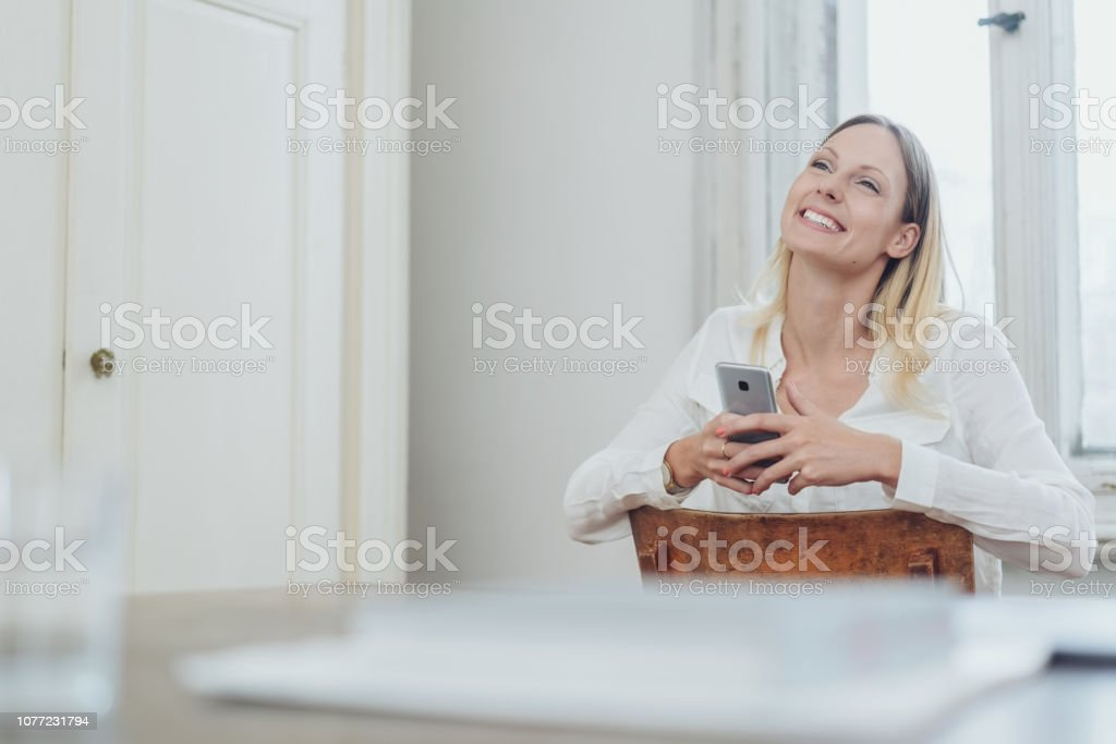 Happy young woman sitting holding a mobile