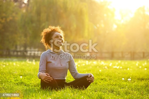 istock Happy young woman sitting in yoga position 478921850