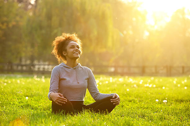 Happy young woman sitting in yoga position Happy young woman sitting outdoors in yoga position wellbeing stock pictures, royalty-free photos & images