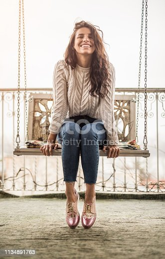 Happy young woman sitting on a swing on a house balcony and day dreaming.
