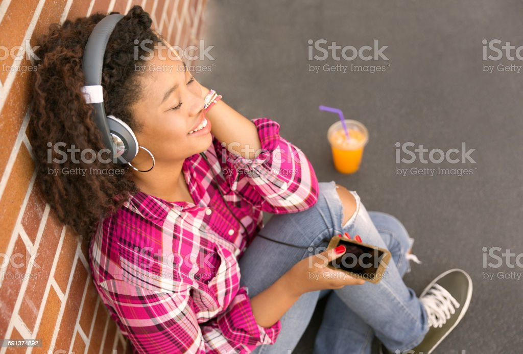happy young woman sitting on ground listening to music stock photo