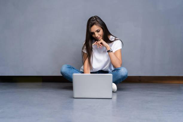 Glückliche junge Frau sitzt auf dem Boden mit gekreuzten Beinen und mit Laptop auf grauem Hintergrund. – Foto