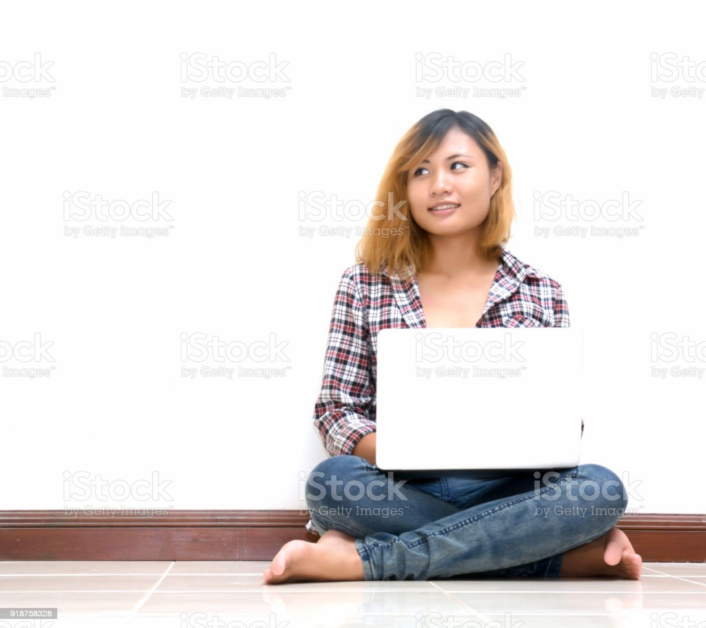 Happy young woman sitting on the floor with crossed legs and using laptop. stock photo