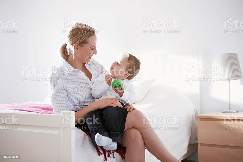 Happy young woman sitting with her son in bedroom royalty-free stock photo