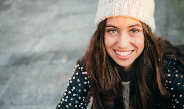 glückliche junge frau lächelnd auf der straße - winterjacke lang damen stock-fotos und bilder