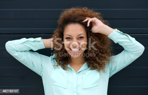 186534921 istock photo Happy young woman smiling outdoors against black background 462163107