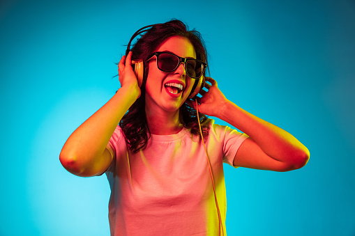 Happy young woman listening to the music and smiling over trendy blue neon studio background. Beautiful female portrait. Concept of human emotions, facial expression, summer holidays or weekend.