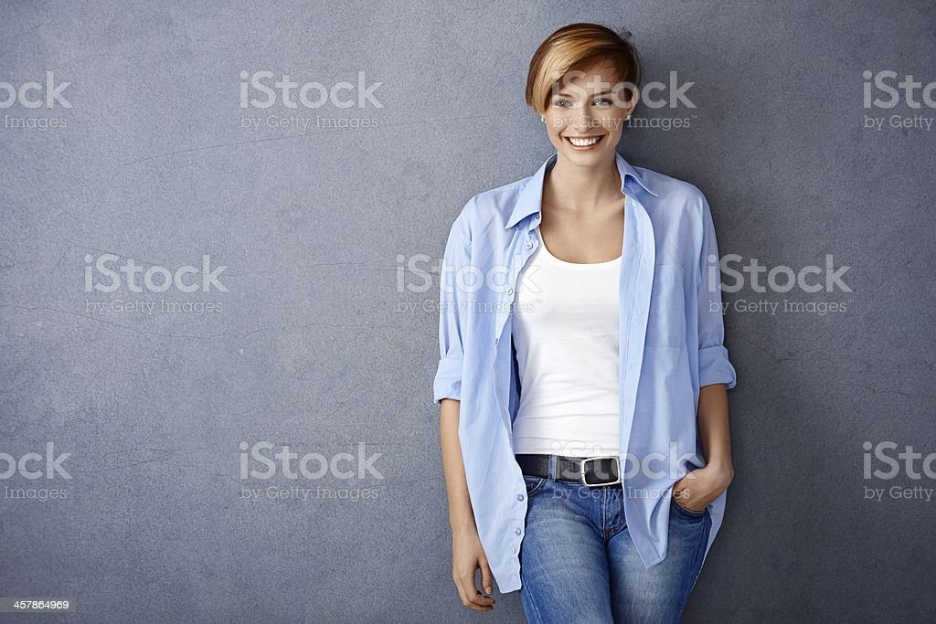 Happy young woman standing by wall stock photo