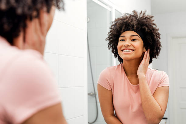 happy young woman standing in front of mirror in bathroom - woman mirror foto e immagini stock